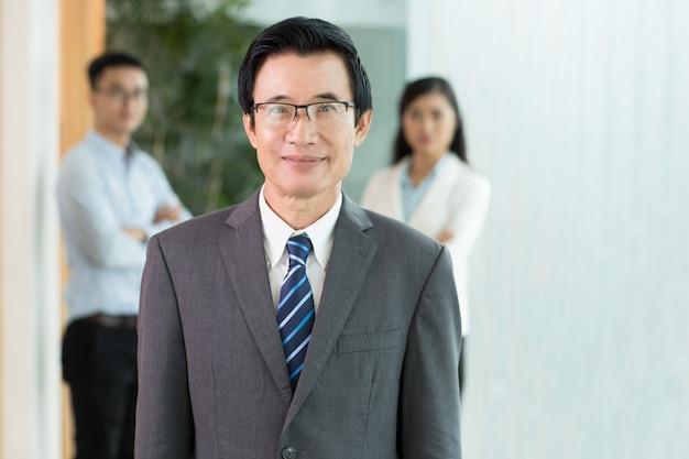 Positive asiatischer älterer geschäftsmann und sein team