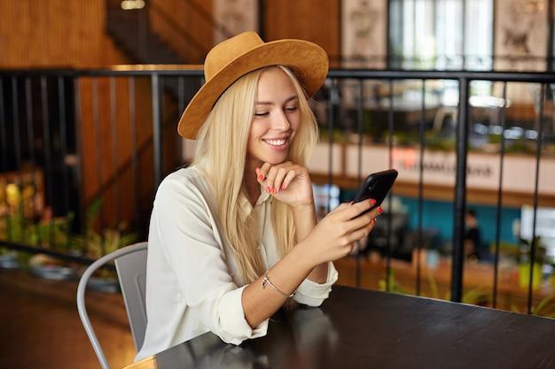 Positive attraktive blonde frau mit langen haaren, die kinn auf ihrer hand halten, während sie ihr smartphone betrachten, über caféinnenraum in braunem hut sitzend