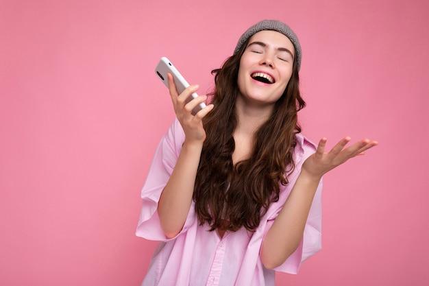 Positive attraktive junge brünette frau mit stylischem rosa hemd und grauem hut isoliert über rosa