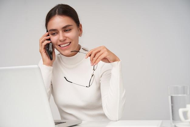Positive attraktive junge dunkelhaarige frau mit natürlichem make-up, die nette telefongespräche hat und brillen in erhabener hand hält, am tisch über weißer wand sitzend