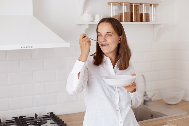 Positive attraktive junge erwachsene frau mit dem dunklen haar, das weißes freizeithemd trägt. frühstücken, teller in den händen halten, wegschauen, vom löffel essen.
