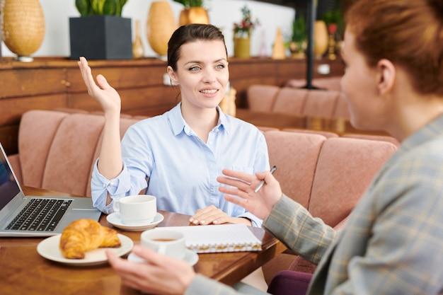 Positive attraktive junge frau, die hand hebt, während sie geschäftspartner im café ideen für startup-projekt anbietet
