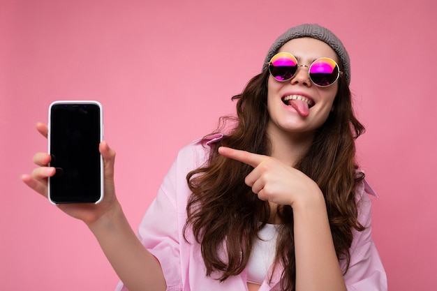 Positive attraktive junge frau, die stilvollen rosa hemd grauen hut und bunt trägt