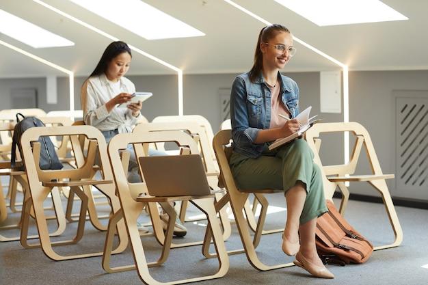 Positive attraktive studentin in brillen, die auf stuhl sitzen und notizen machen, während sie mit lehrer sprechen