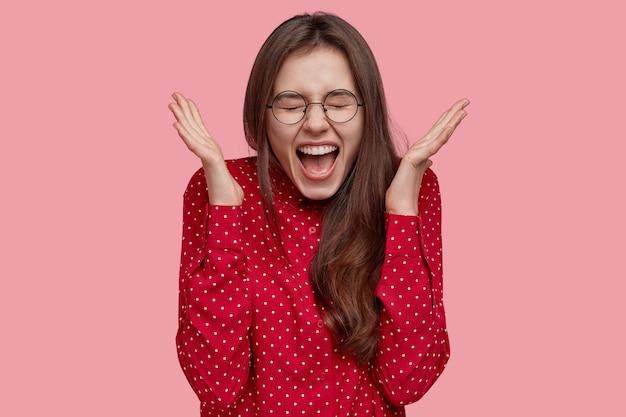 Positive aufgeregte frau breitet hände aus, schreit vor glück, fühlt sich aufgeregt und überglücklich, trägt modische rote bluse