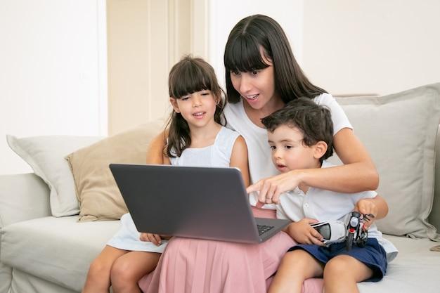 Positive aufgeregte mutter, die zwei kinder umarmt und auf laptop-anzeige zeigt. familie sitzt auf der couch zu hause und schaut film.