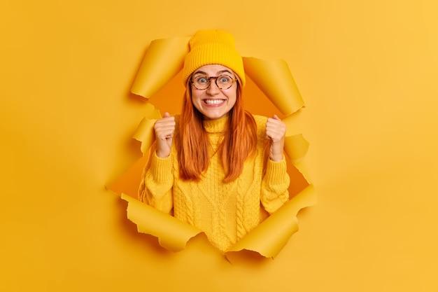 Positive aufgeregte rothaarige frau hebt fäuste, trägt gelben hut und gestrickten pullover, drückt freude aus, bricht durch papierwand
