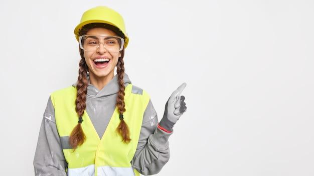 Positive baumeisterin auf der baustelle zeigt etwas über leerzeichen, trägt schutzbrillen mit schutzhelm, uniform hat ingenieurkarriere isoliert über weißer wand. sicherheitskleidung