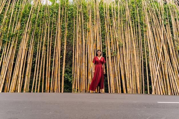 Positive begeisterte junge brünette frau, die in der nähe von bambuspflanzen steht und ihren urlaub auf der insel verbringt