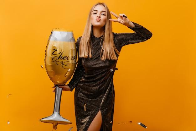 Positive blonde frau, die mit großem weinglas aufwirft. entzückende weiße frau im kleid, das für geburtstagsfeier vorbereitet.