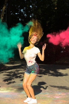 Positive blonde frau, die mit leuchtenden farben springt, die um sie herum explodieren