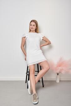 Positive blonde frau posiert im innenstudio in weißem outfit