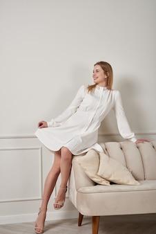 Positive blonde frau sitzt auf einem weißen sofa in einem weißen kleid