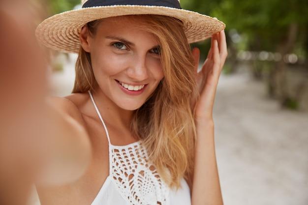 Positive blonde junge frau mit fröhlichem ausdruck macht selfie als posen im freien auf tropischer insel, trägt modischen sommerhut und weißes kleid