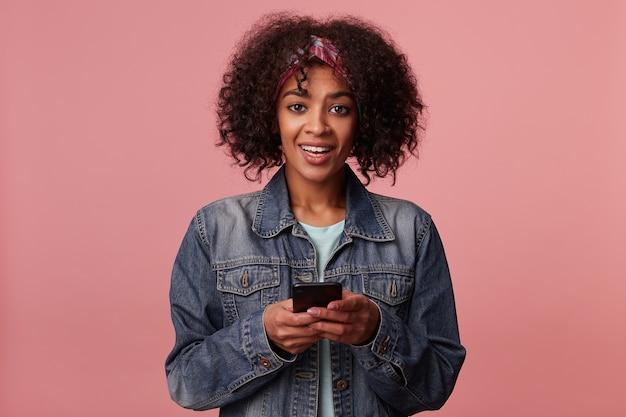 Positive braunäugige junge dunkelhäutige dame mit lockigem braunem haar, die das mobiltelefon in erhobenen händen hält und mit breitem lächeln schaut, minz-t-shirt und jeansmantel tragend