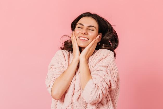 Positive brünette in guter stimmung lacht und berührt ihre wangen. mädchen im gestrickten kleid, das auf rosa hintergrund aufwirft.