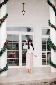 Positive brünette junge frau mit wunderkerze, die nahe verziert für weihnachtshaus steht und weihnachtsfeiertag feiert.