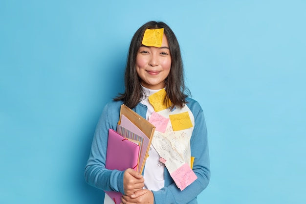 Positive brünette sekretärin trägt ordner mit dokumenten trägt blauen pullover mit haftnotizen geschrieben summen.