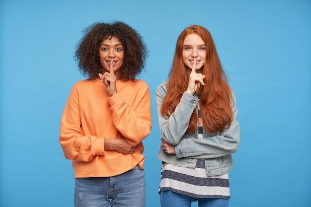 Positive charmante frauen in freizeitkleidung heben die zeigefinger an den mund und schauen fröhlich über die blaue wand