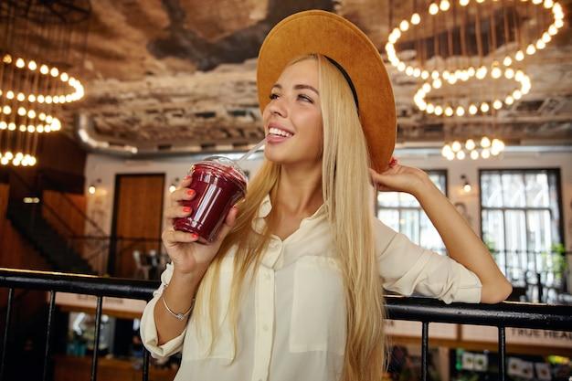 Positive charmante junge blonde frau mit langen haaren, die smoothie mit stroh trinken und verträumt mit aufrichtigem lächeln beiseite schauen, breiten braunen hut und weißes hemd tragend