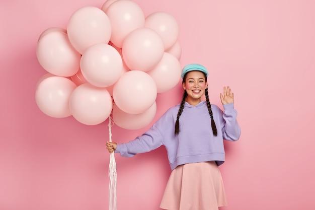 Positive chinesische frau kommt auf freundgeburtstagsfeier, grüßt gefährten, hat dunkles haar in zwei zöpfen gekämmt, gekleidet in lässigem outfit
