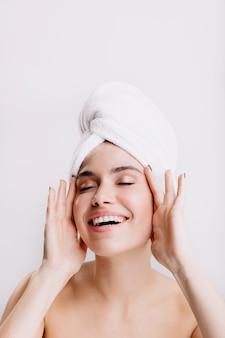Positive dame genießt morgendliche spa-behandlung. mädchen nach der dusche, die auf isolierter wand aufwirft.