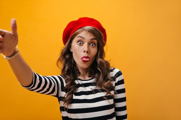 Positive dame in roter baskenmütze zeigt zunge und macht selfie. lustige frau in gestreifter trendiger bluse und roter baskenmütze, die auf orange hintergrund aufwirft.