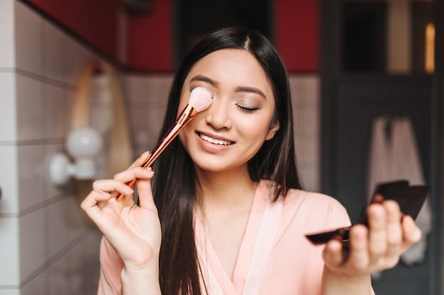 Positive dame mit dunklen haaren bedeckt ihre augen mit make-up-pinsel und posiert im badezimmer