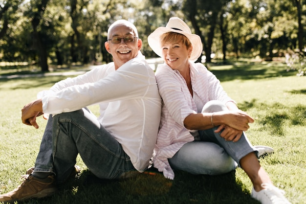 Positive dame mit kühlem hut in gestreifter stilvoller bluse und jeans lächelnd und sitzend auf gras mit mann in brille und hellem hemd im freien.