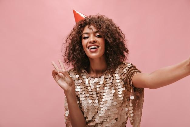 Positive dame mit welligem haar in urlaubsmütze und glänzendem kleid mit friedenszeichen und foto an isolierter rosa wand..