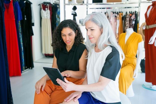 Positive damen sitzen zusammen und benutzen tablet, diskutieren kleidung und einkäufe im modegeschäft. konsum- oder einkaufskonzept