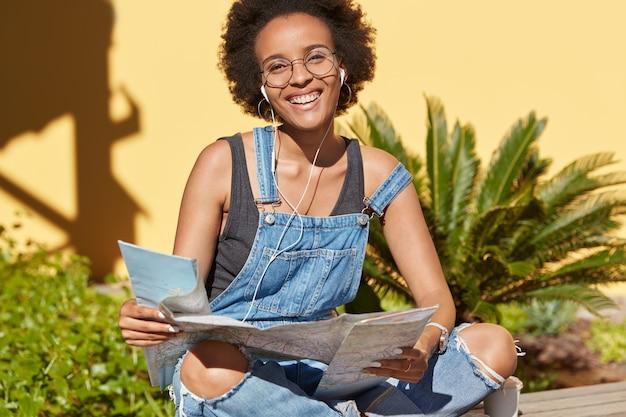 Positive dunkelhäutige dame mit afro-frisur, hält karte, genießt urlaubsreise, möchte einige ziele erreichen, trägt lässige overalls, modelle im freien in tropischer umgebung. menschen und reisen