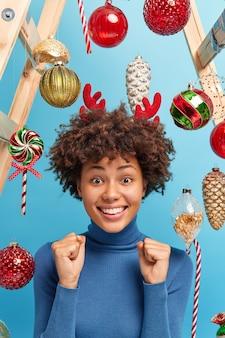 Positive dunkelhäutige frau mit lockigem haar in lässigen rollkragenbällen fäuste erwartet für wunder bereitet sich auf weihnachtsferien vor lässig gekleidet posiert drinnen über neujahrsspielzeug. festliche veranstaltung.