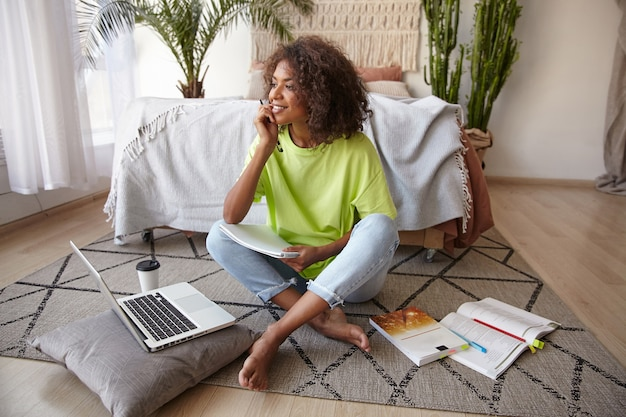 Positive dunkelhäutige junge frau mit lockigem haar, die mit gekreuzten beinen auf dem boden sitzt und träumerisch beiseite schaut, während sie studiert, freizeitkleidung trägt
