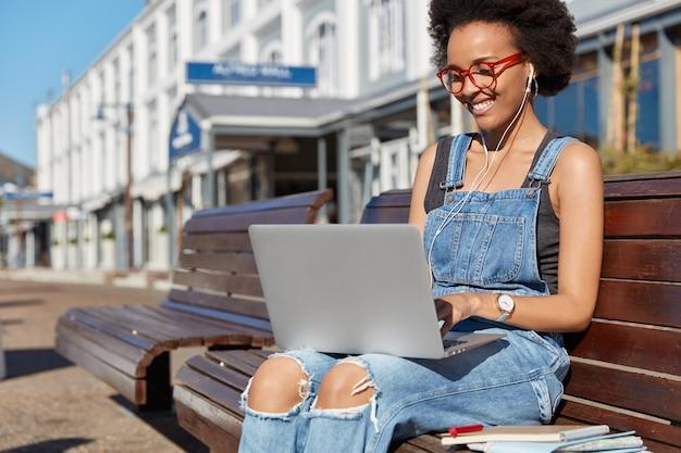 Positive dunkelhäutige mädchenreisende blogger genießt online-kommunikation, tätigt videoanrufe, gespräche mit freunden aus dem ausland, benutzt laptop, kopfhörer, sitzt auf einer bank in der nähe des bahnhofs und wartet auf den transport