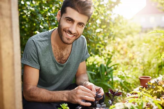 Positive emotionen, ländlicher lebensstil. außenporträt des jungen bärtigen hispanischen bauern, der mit zähnen lächelt, in seinem garten arbeitet, samen pflanzt, pflanzen gießt.
