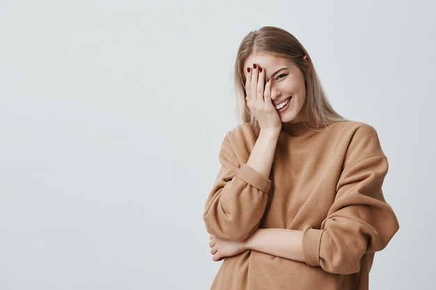 Positive entzückende weibliche model lächelt glücklich mit langen blonden haaren, freut sich über angenehme neuigkeiten, hält die hand auf dem kopf, trägt beige lose kleidung. konzept für menschen, stil und emotionen.