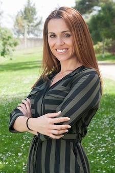 Positive erfolgreiche geschäftsfrau, die im park aufwirft