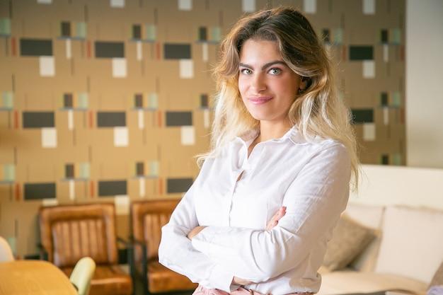 Positive erfolgreiche geschäftsfrau, die mit verschränkten armen im innenraum der zusammenarbeit oder des coffeeshops aufwirft, kamera betrachtet und lächelt