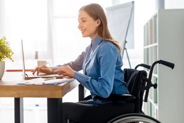 Positive erwachsene frau, die im büro arbeitet
