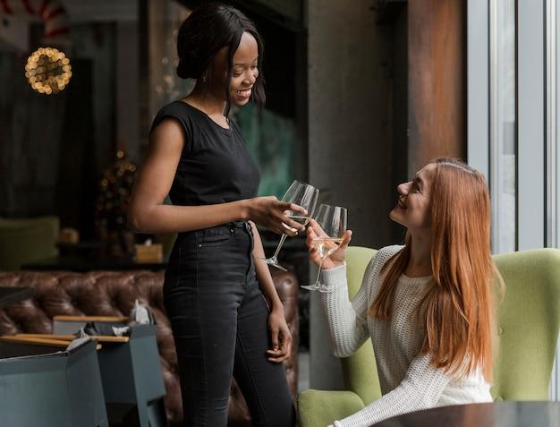 Positive erwachsene frauen, die ein glas wein genießen
