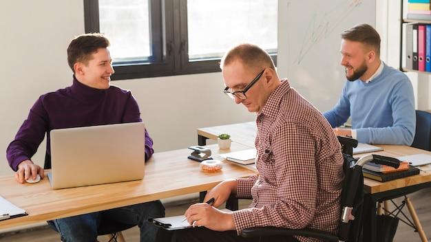 Positive erwachsene männer, die im büro zusammenarbeiten