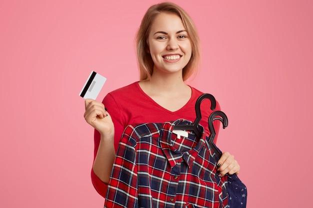 Positive europäische dame mit zahnigem lächeln, hält kleidung auf kleiderbügeln und plastikkarte, zahlt für neues outfit, genießt online-shopping, ist in hochstimmung, isoliert über pink. zahlung