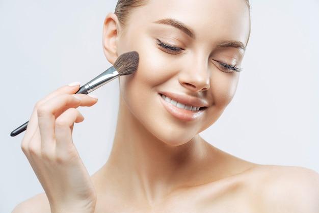 Positive europäische frau mit gesunder weicher haut, verwendet kosmetischen puderpinsel