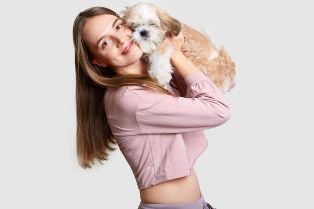 Positive europäische frau mit langen haaren umarmt ihr lieblingshaustier mit flauschigem fell, gekleidet in lässiges oberteil, zeigt nackten bauch, ist in guter form, mag tiere, isoliert auf weiß