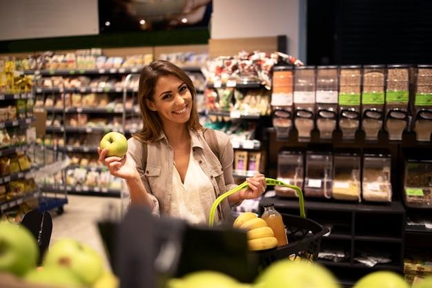 Positive frau, die apfelfrucht im supermarkt hält