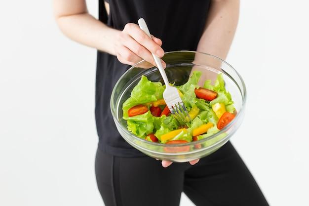 Positive frau, die einen leichten griechischen salat isst