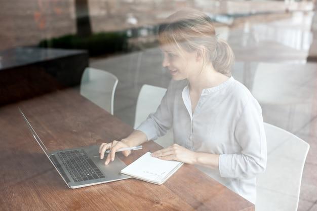 Positive frau, die laptop verwendet und kenntnisse macht