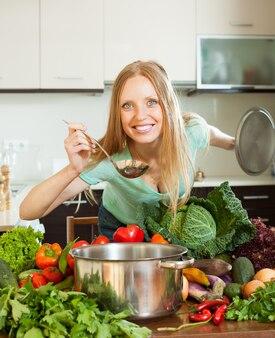 Positive frau, die mit schöpflöffel vom rohen gemüse kocht