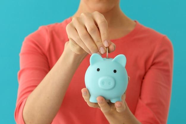 Positive frau, die münze in sparschwein einsetzt, planungsbudget, finanzielle einsparungen